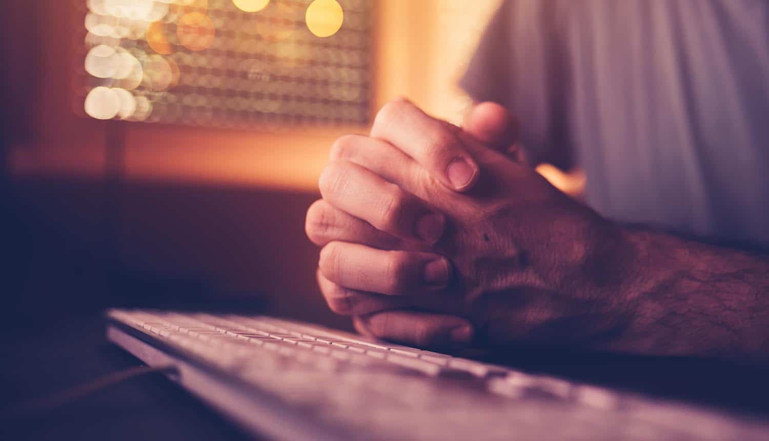 Man praying in front of computer showing the survey on remote workers adhering to company's security protocols