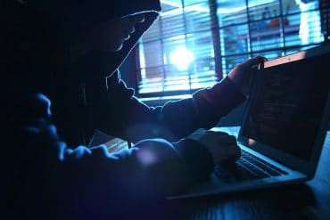 Hacker working on laptop showing the extent of underground hack-for-hire services with the unmasking of Dark Basin group