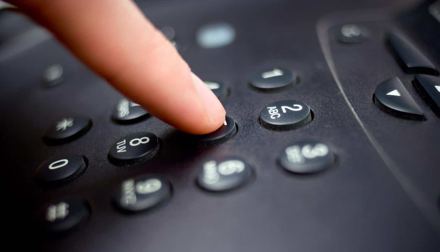 Hand dialling on telephone keyboard showing 100,000 inboxes of remote workers fallen victim to voicemail phishing attacks