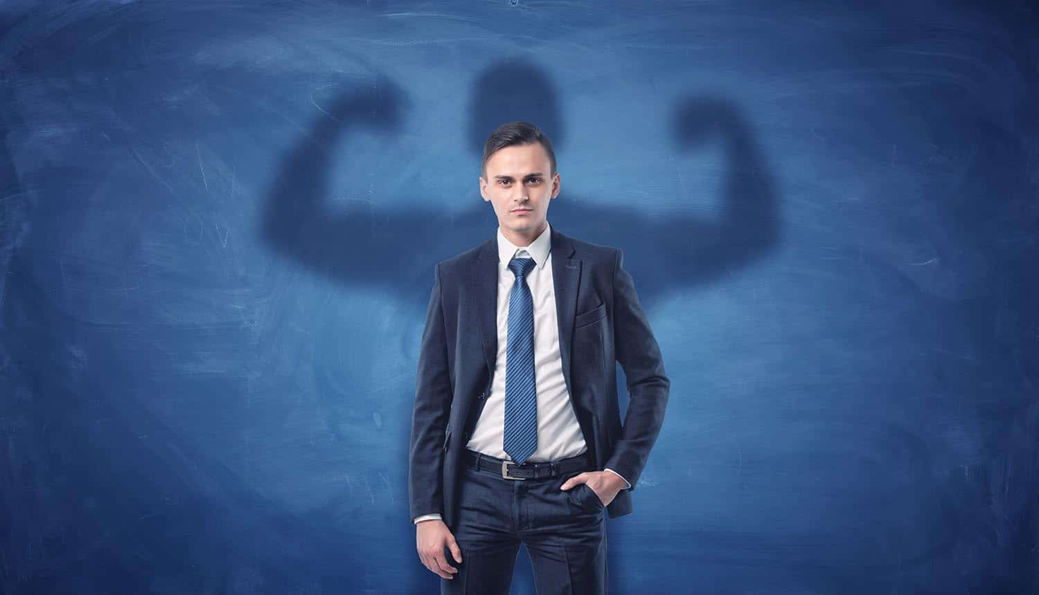 Businessman casting shadow of big strong muscular man