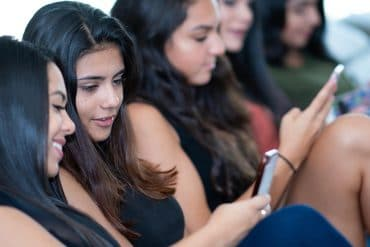 Teenage girls using smartphones showing the India ban on Chinese apps due to national security reason