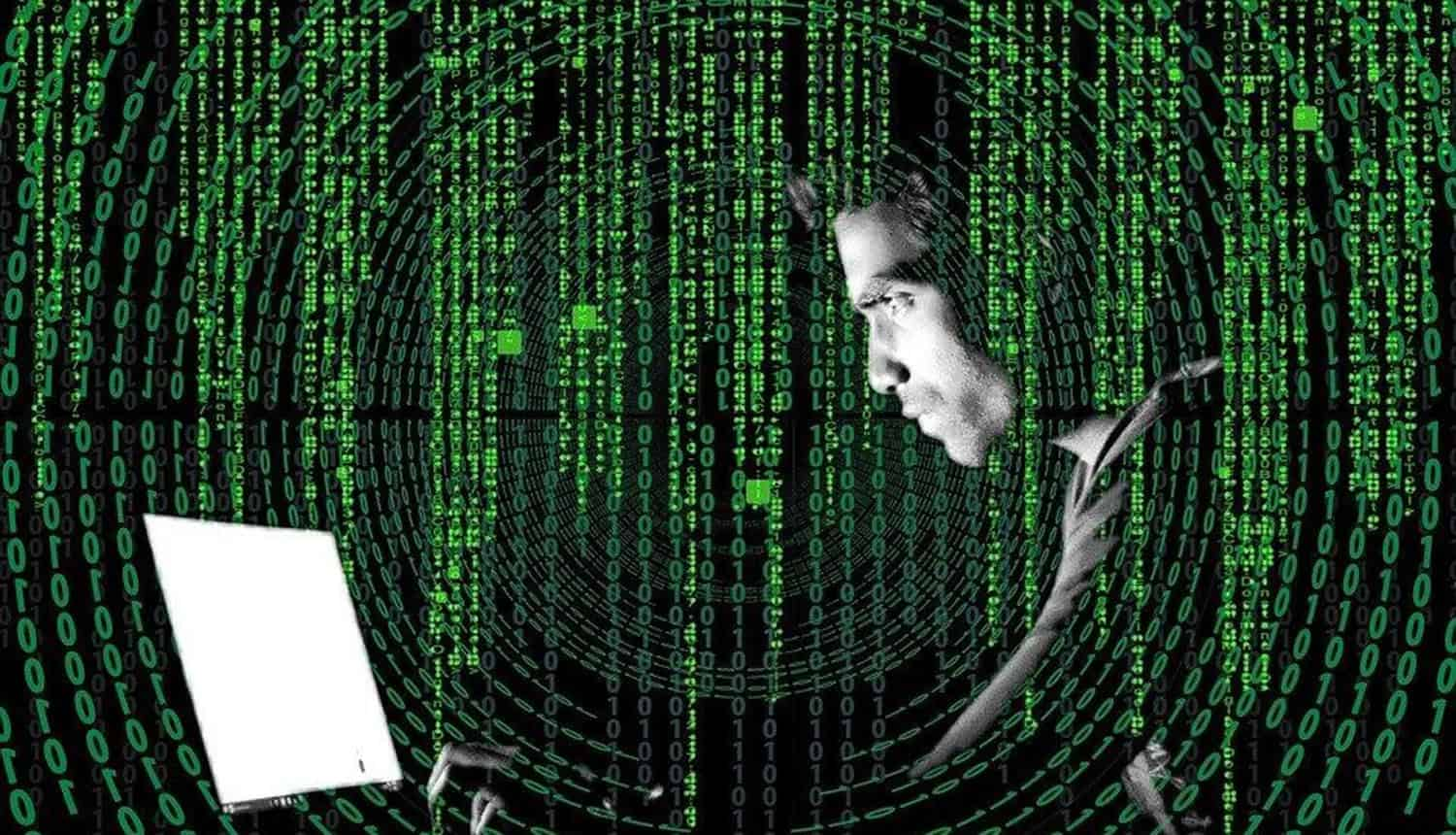 Hacker working on laptop showing need for data protection technologies