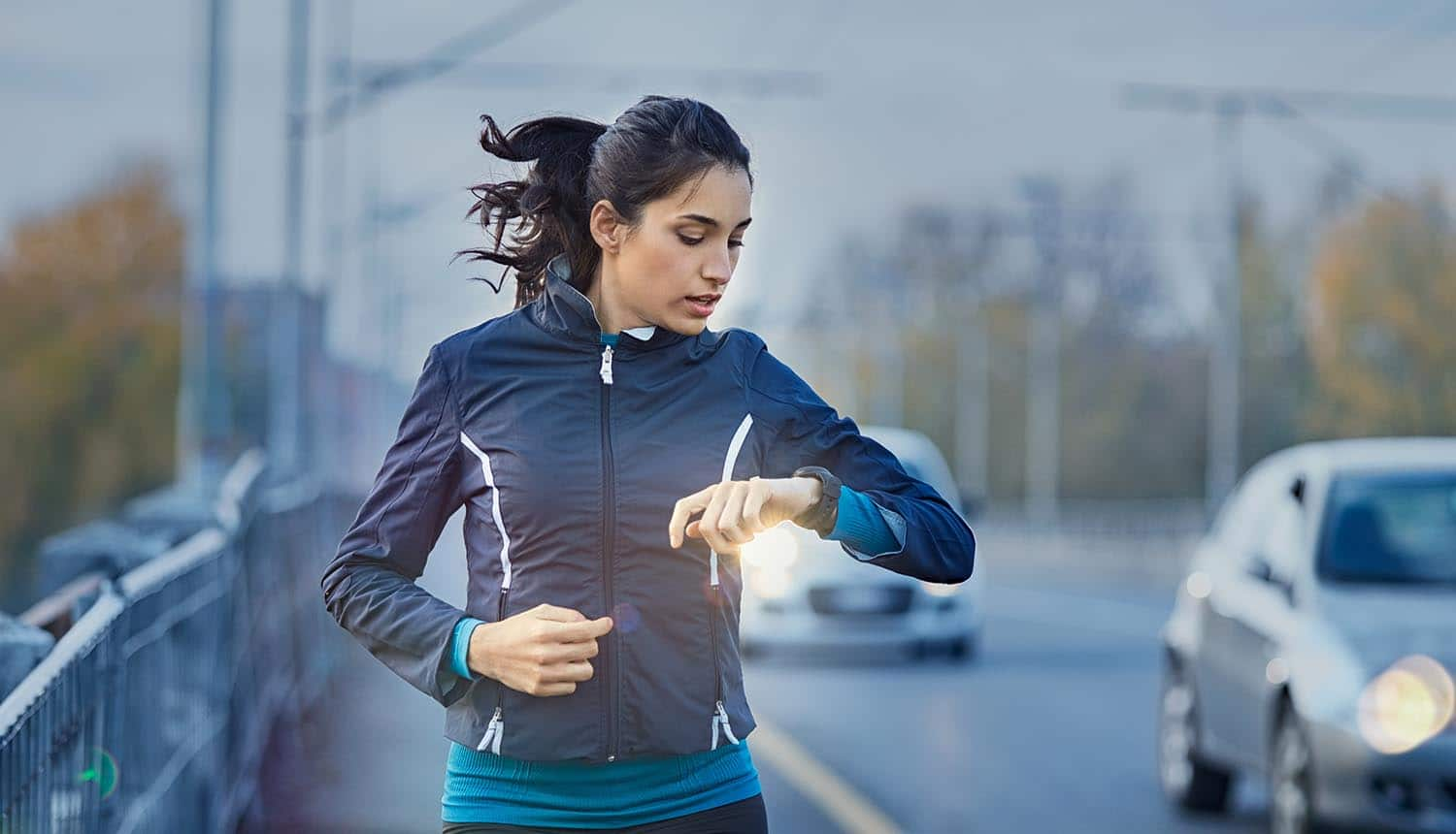 Woman jogger looking at smart watch showing the concerns over Google's access to health data through the proposed acquisition of Fitbit