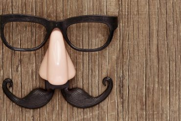 Fake mustache, nose and eyeglasses on a rustic wooden surface showing impact of deepfakes
