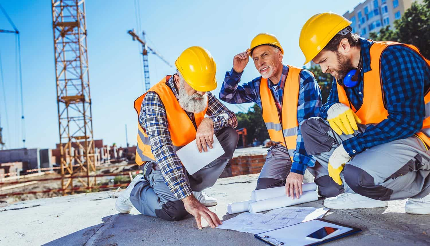 Three construction workers sitting on concrete at construction site