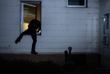 Burglar entering a house through a window showing privacy risks of home security cameras