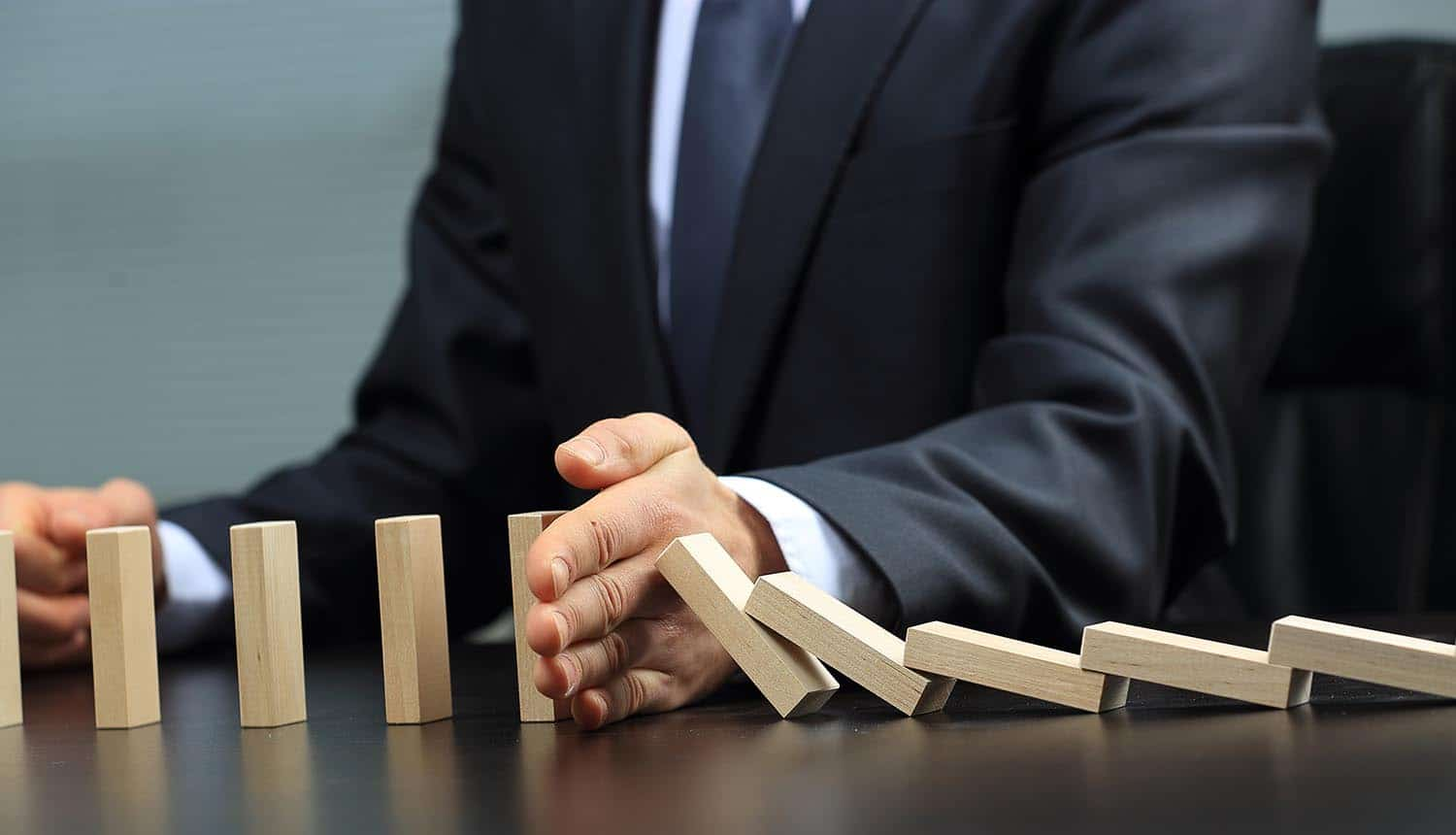 Hand stopping wooden blocks from falling showing the need for companies to measure data privacy risks