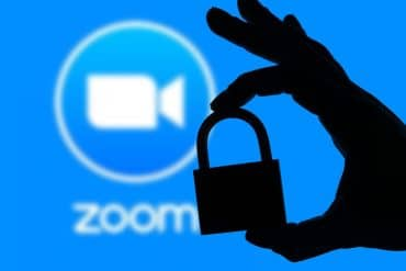 Hand holding padlock with Zoom app logo showing the need to give up personal information for Zoom users to enable end-to-end encryption