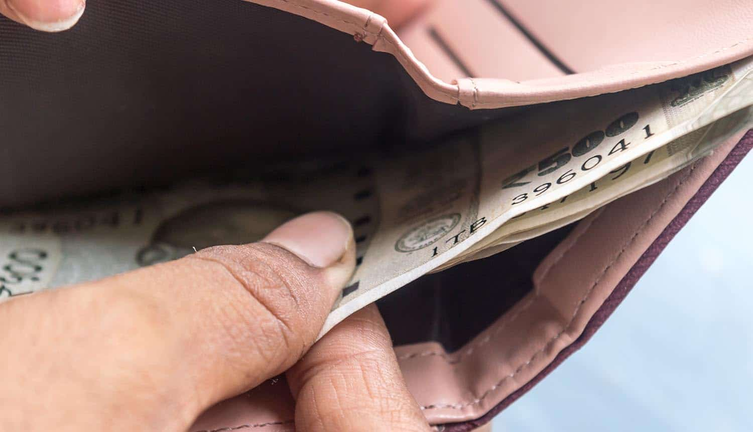 Woman taking out banknotes from leather wallet showing risks in Bitcoin
