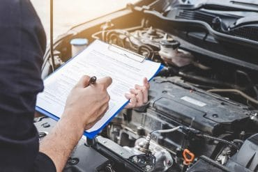 Automobile mechanic repairman checking a car engine with checklist showing need for CCPA compliance