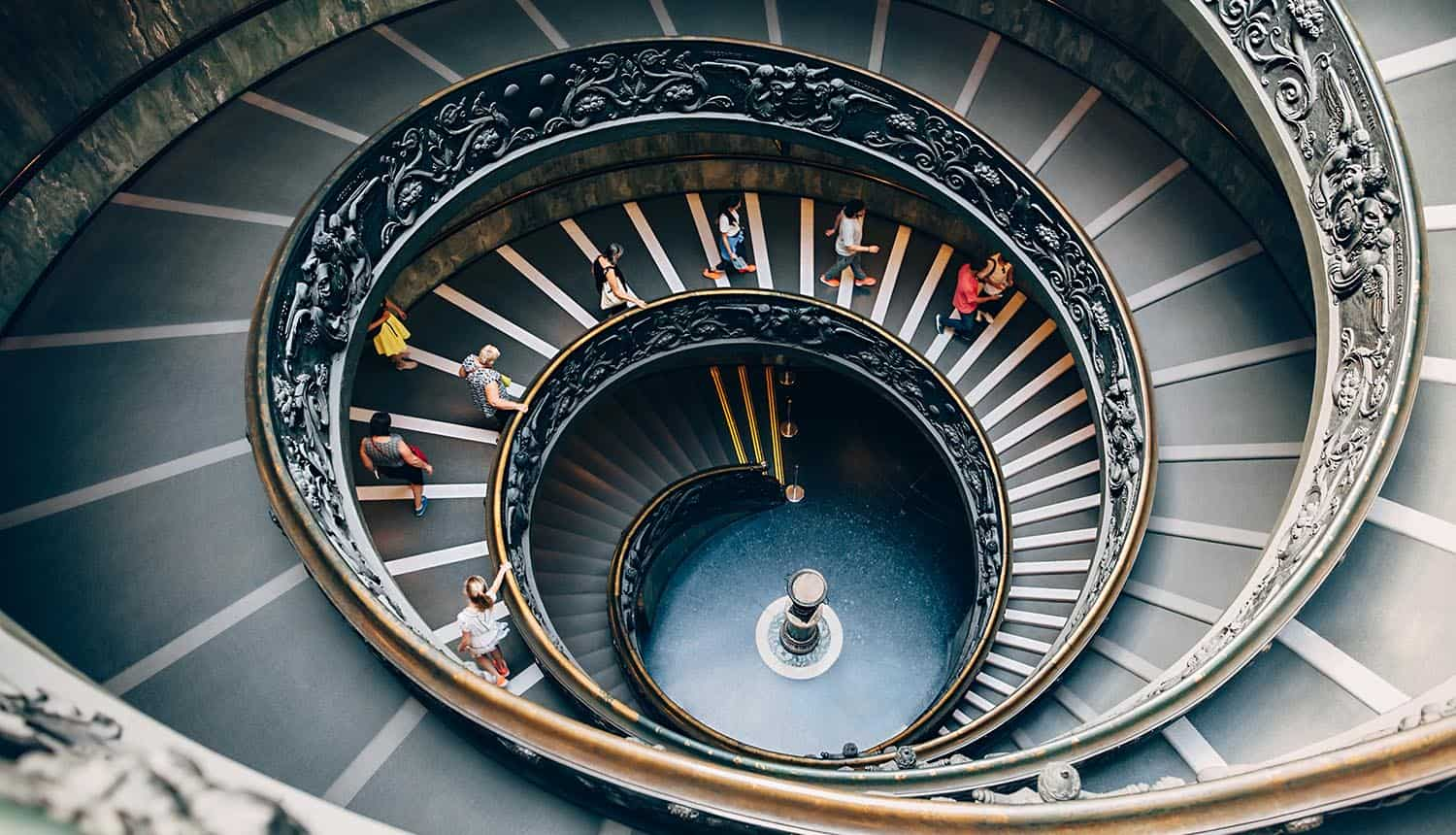 People climbing down the spiral stairs of the Vatican Museums showing threat of Chinese hackers