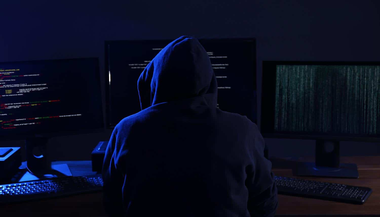 Hacker with computers in dark room showing Experian data breach