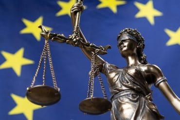Statue of the Goddess of Justice against EU flag showing reliance on SCCs with Privacy Shield gone