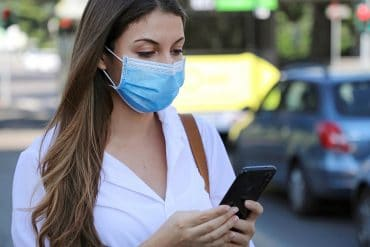 Young woman wearing surgical mask using smart phone app showing lack of data protection impact assessment for UK Test and Trace, in violation of GDPR