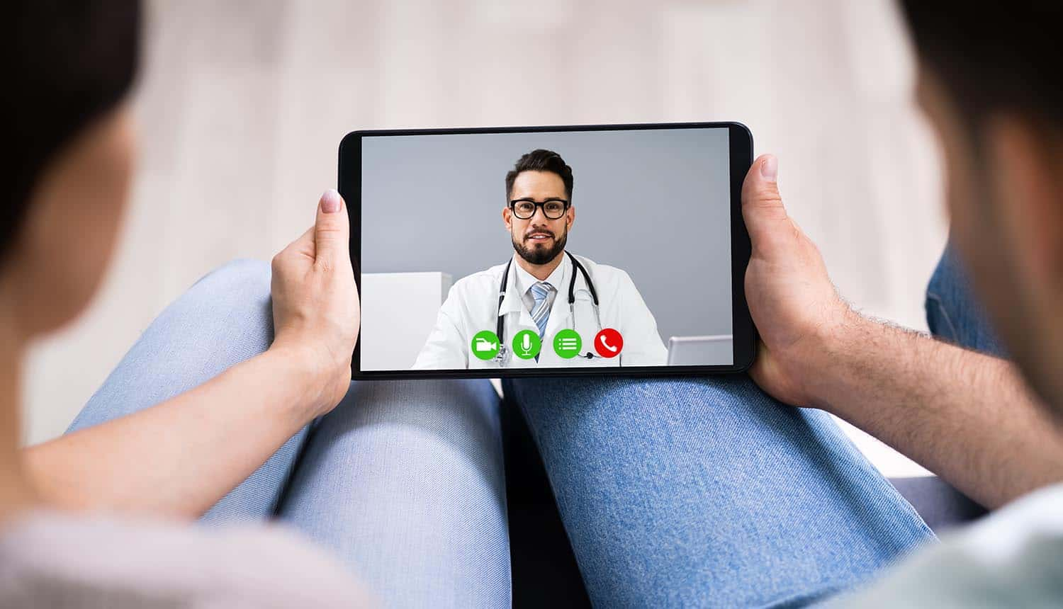 Couple using telehealth services in video conference call with doctor showing increased cyber threats