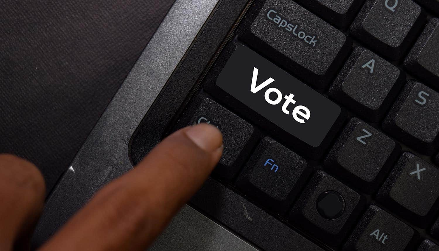 Key with text Vote on laptop keyboard showing danger of data breach of electoral voter data
