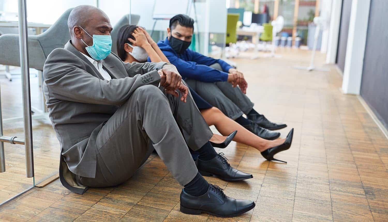 Tired SMB security teams with face mask sit on floor of office