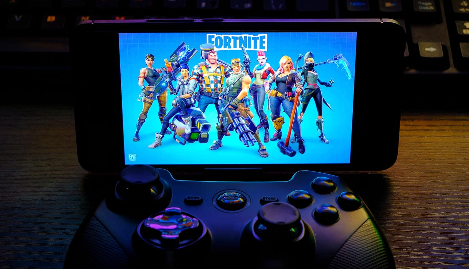 Joystick and mobile phone with the logo of the popular game showing black market for Fortnite accounts