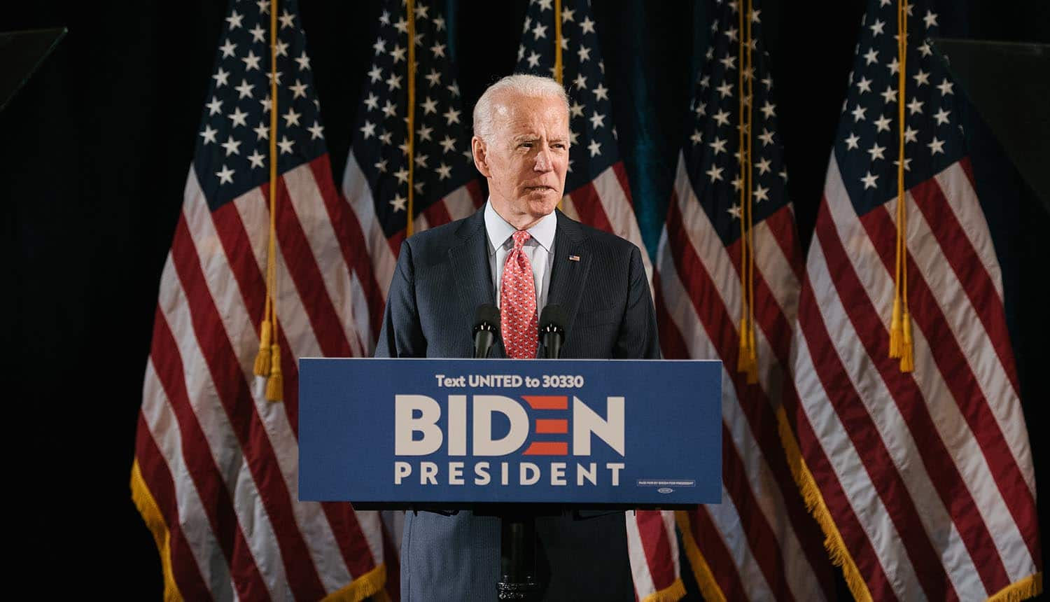 2020 election candidate Joe Biden on podium showing hacker groups targeting Trump and Biden campaigns