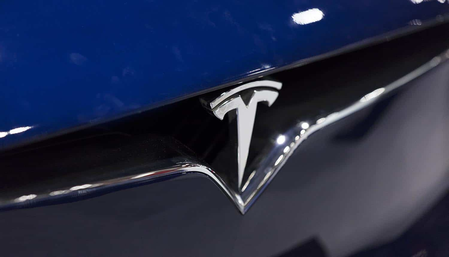 Close up of a Tesla car badge showing Russian hacker's plan for ransomware attack