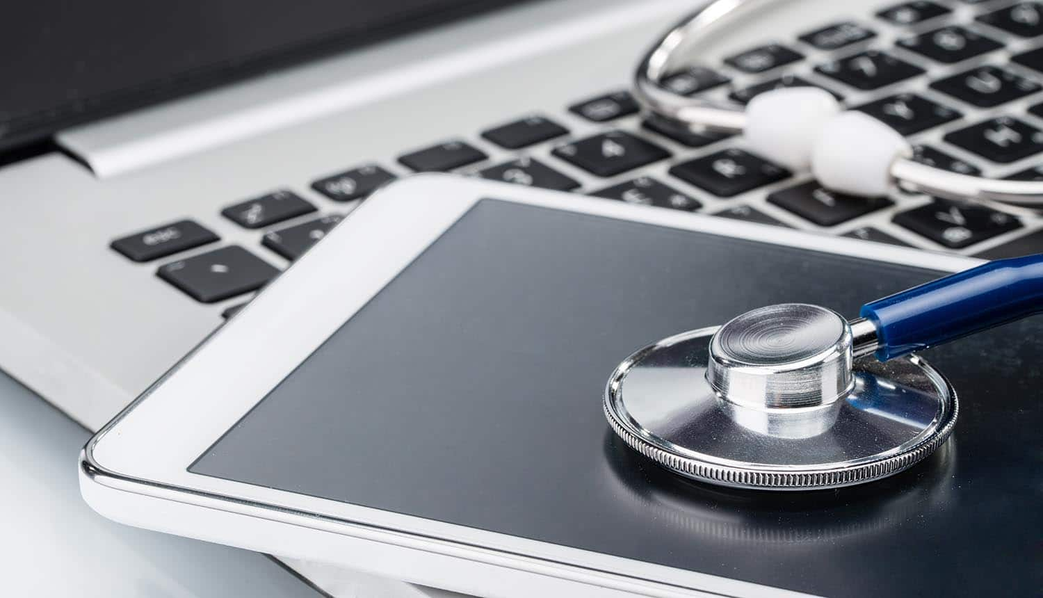 Stethoscope on tablet and laptop keyboard showing need to focus on hardware security risks