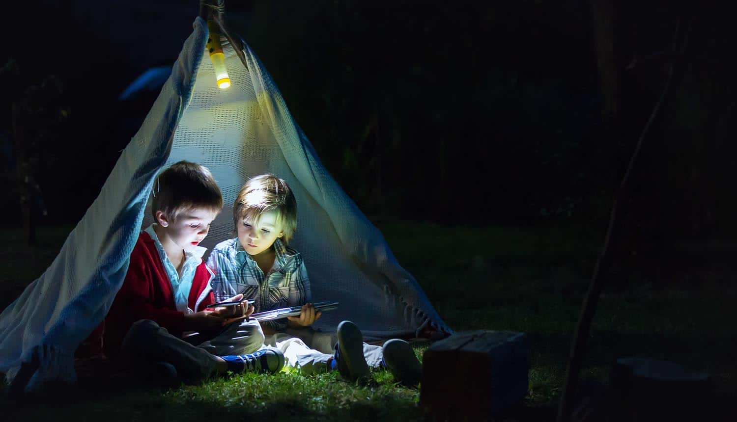 Children using tablet and mobile phone at night in campside showing need for digital identity and age verification