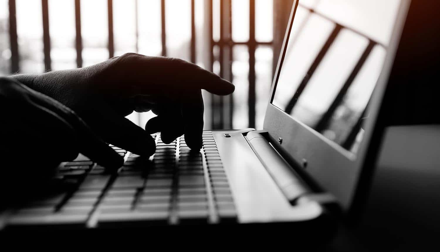 Hands typing on laptop showing insider threats