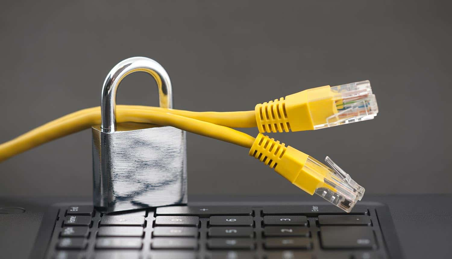 Padlock on network cables on computer keyboard showing benefits of VPNs