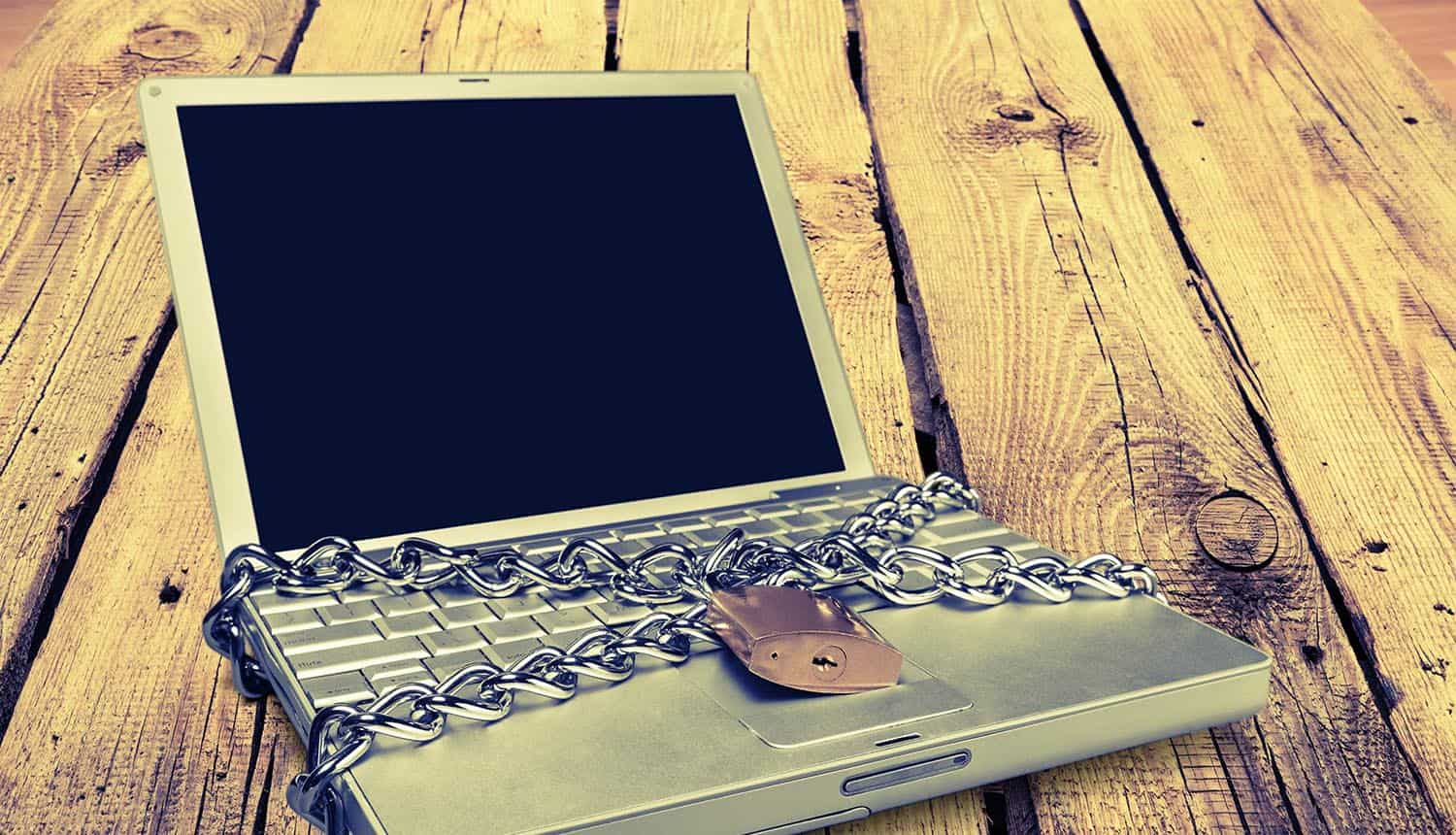 Chain and lock over laptop showing need to secure online education