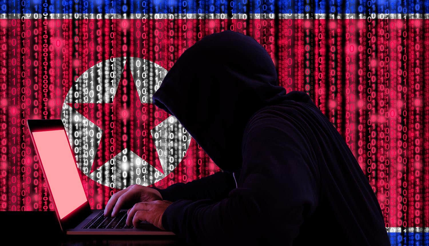North Korean hacker sitting in front of laptop with digital North Korean flag in background conducting cyber attacks