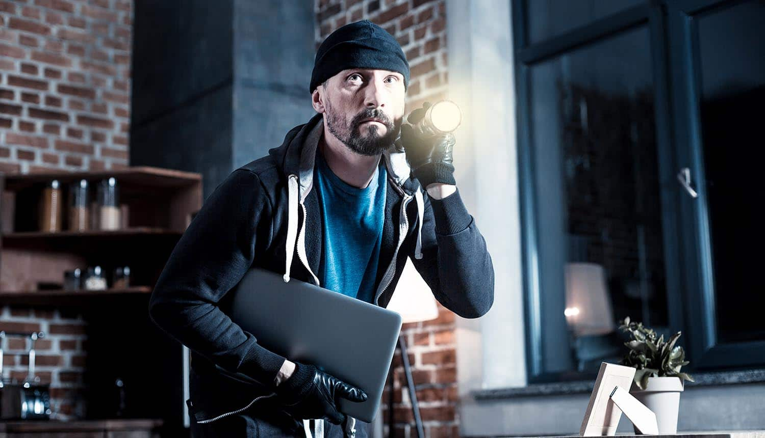 Professional burglar wearing black gloves and holding a torch showing data theft