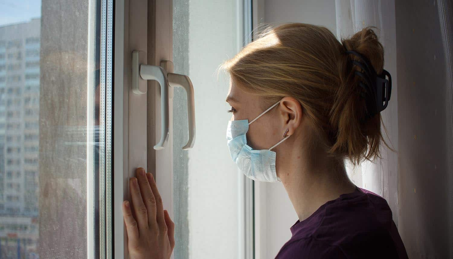 Woman with medical mask looks outside window