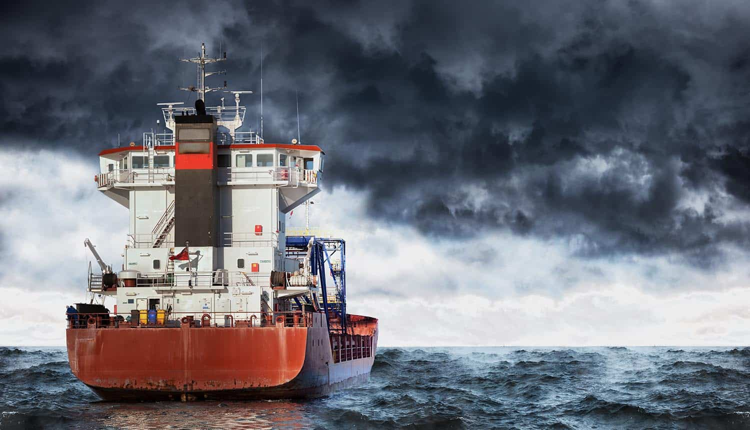Cargo ship at sea during a storm showing business risk of cyber attacks