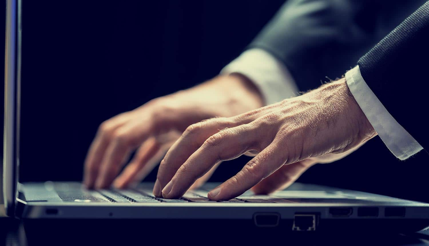 Close up of businessman typing on laptop showing insider threats