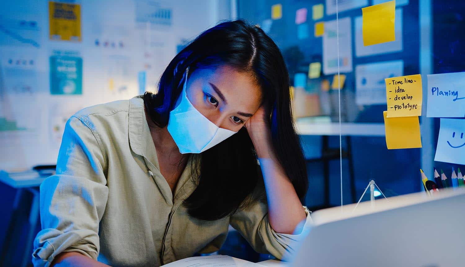Women with face mask using laptop showing increase cyber attacks on remote work during COVID-19