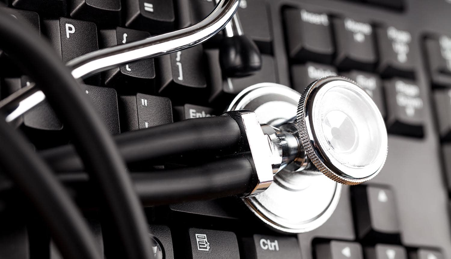 Stethoscope on laptop showing ransomware attack impacting clinical trials
