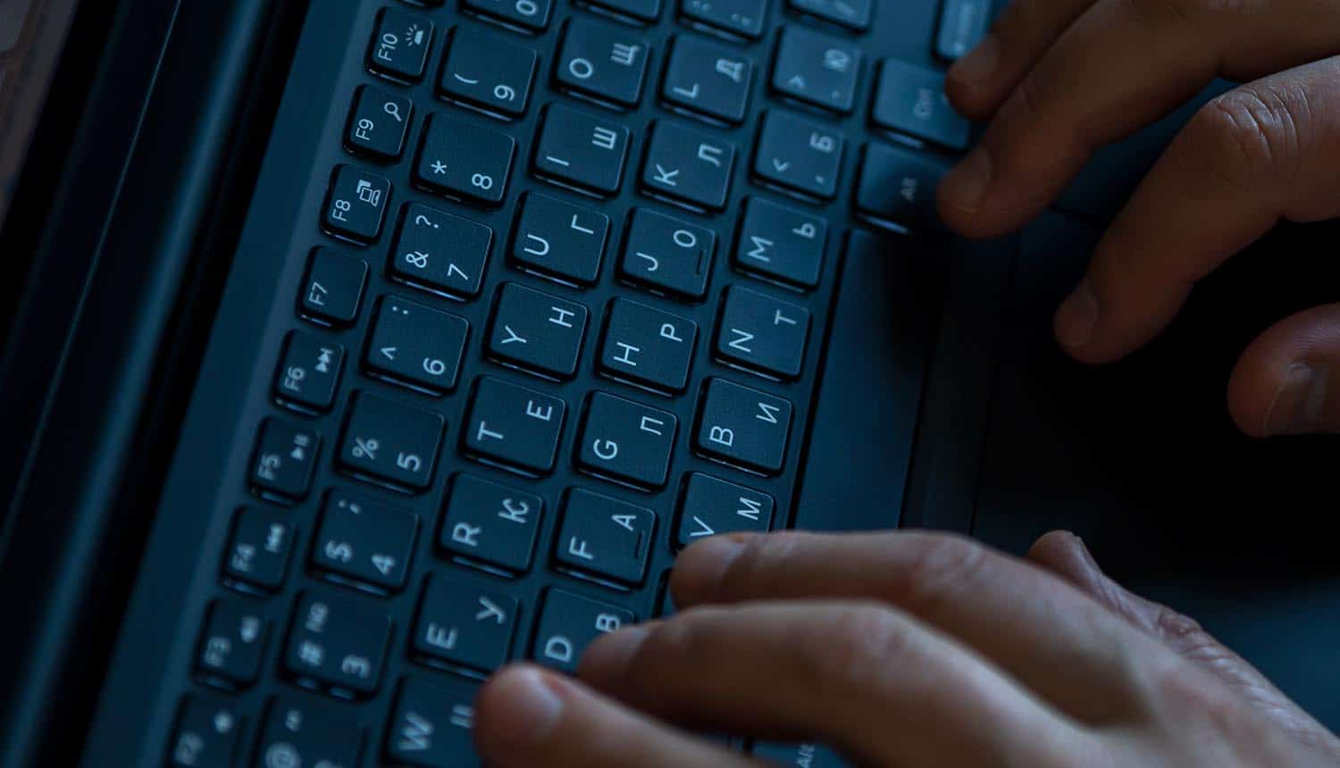Hands on a laptop keyboard showing REvil ransomware offer on hacker forum