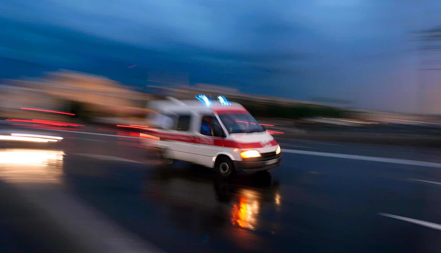Ambulance car speeding blurred motion showing disruption of healthcare services due to Ryuk ransomware attack