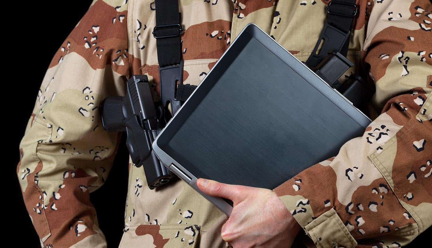 Armed male soldier holding laptop computer showing threat of cyber war