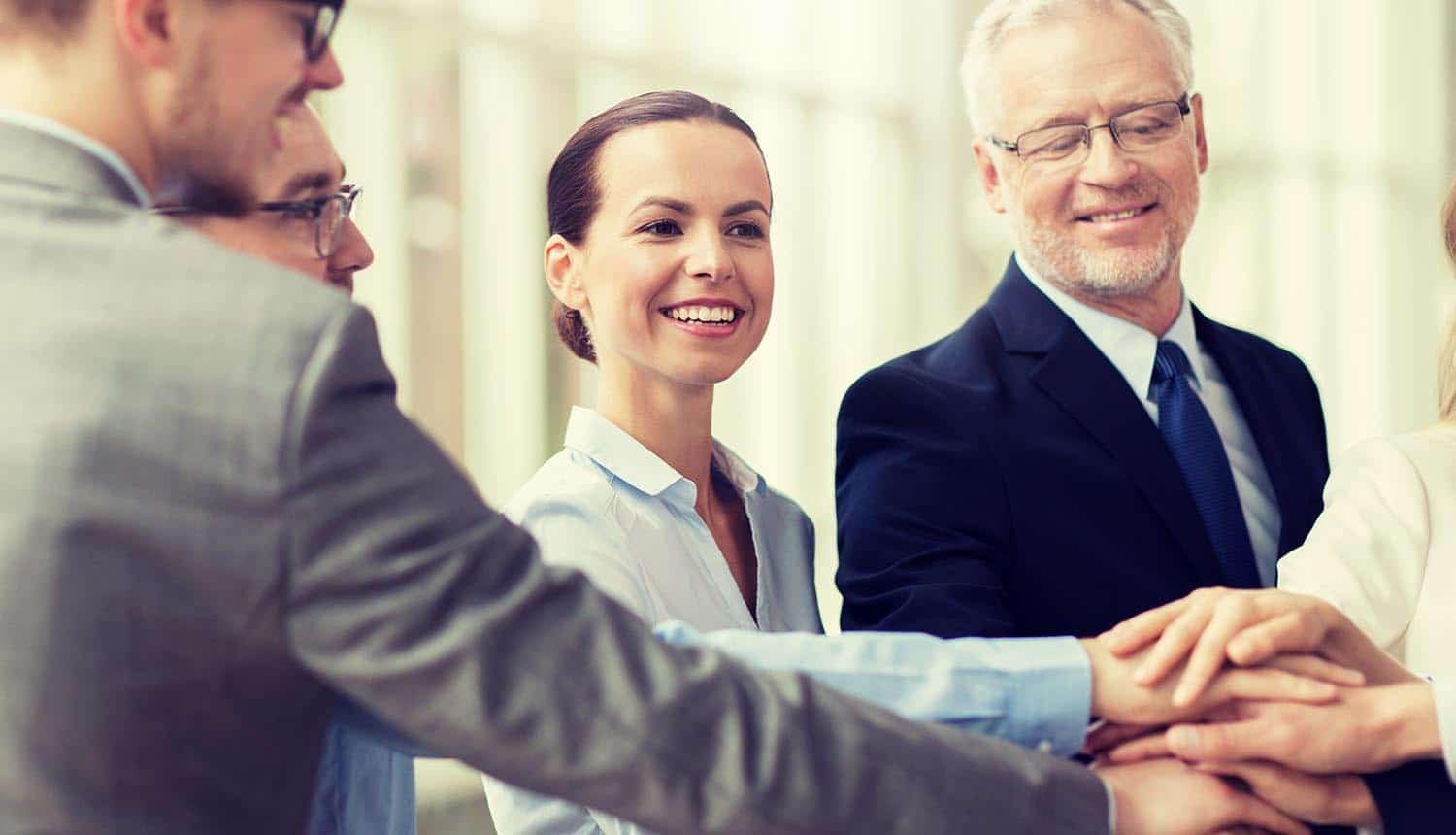 Smiling business people putting hands on top of each other in office