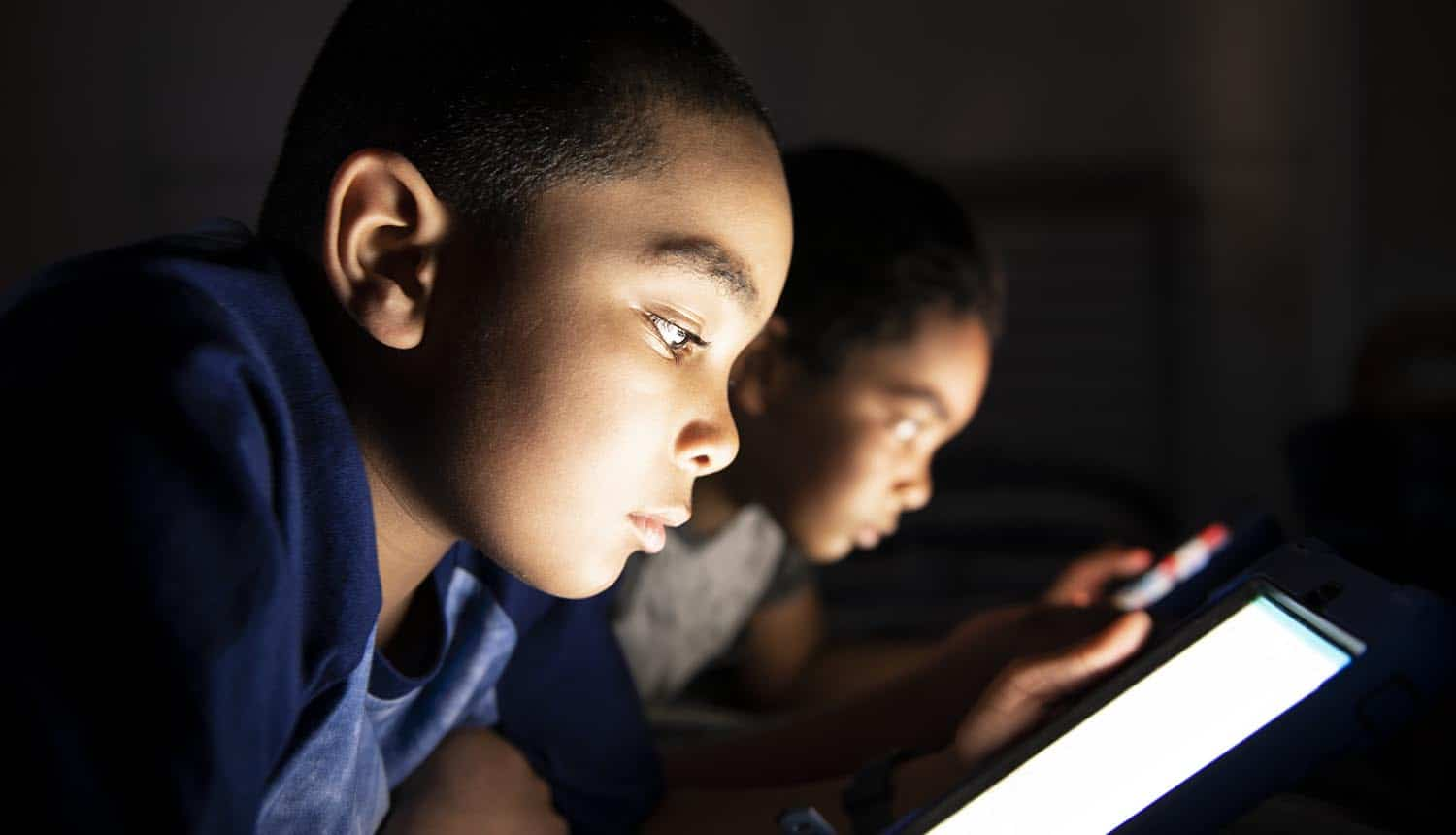 Two boys playing with tablet on the bed showing data breach of online kids' game