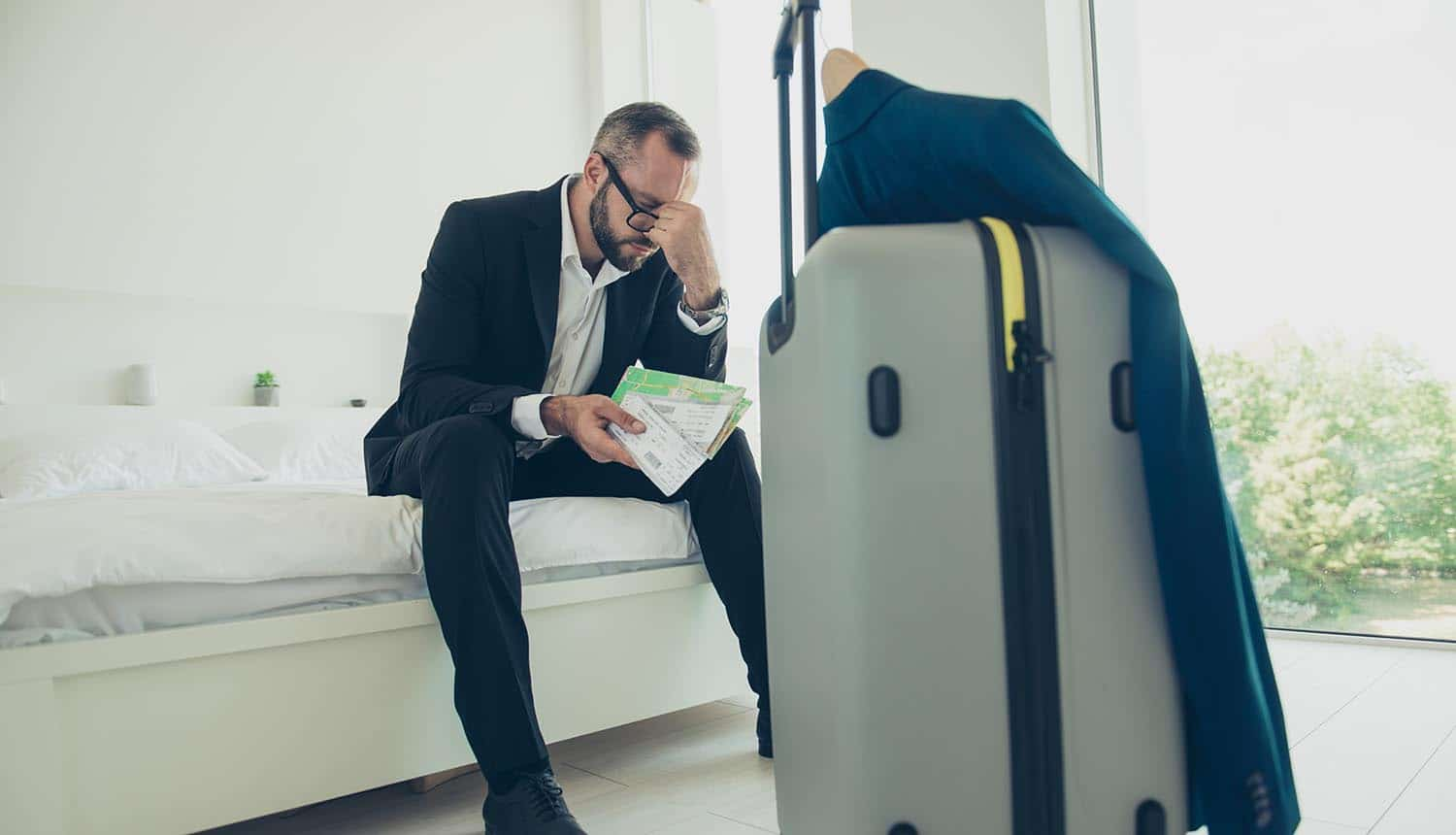 Frustrated businessman sitting with his luggage showing data leak of hotel booking companies
