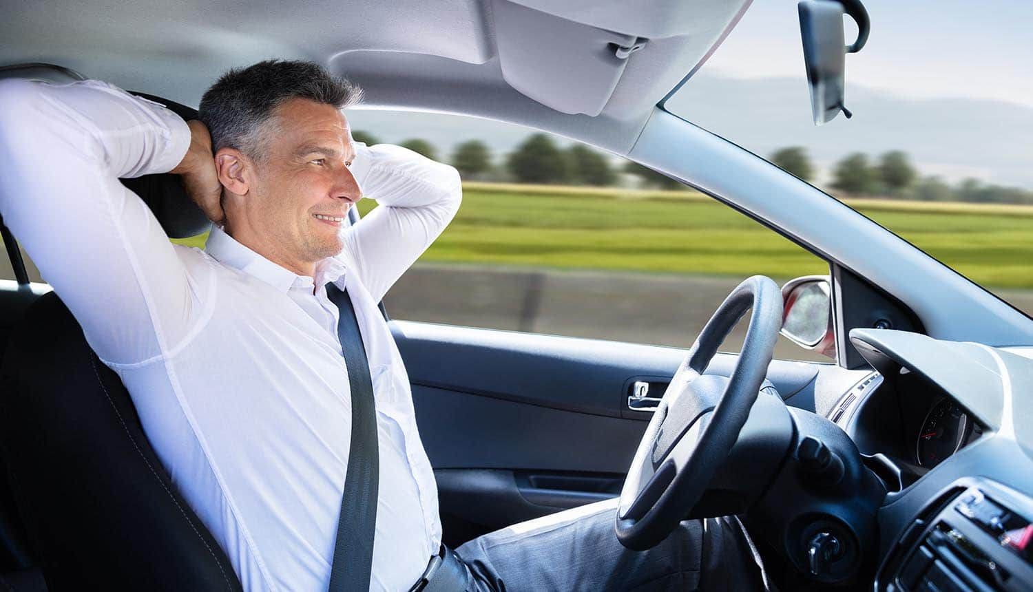 Relaxed man sitting in an autonomous car showing increasing importance of security