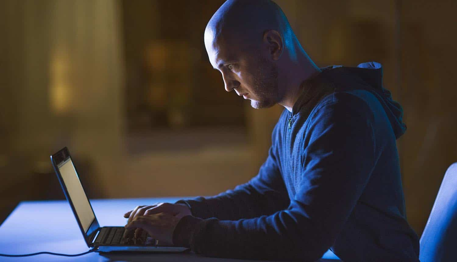 Hacker in dark room using laptop computer for cyber attack