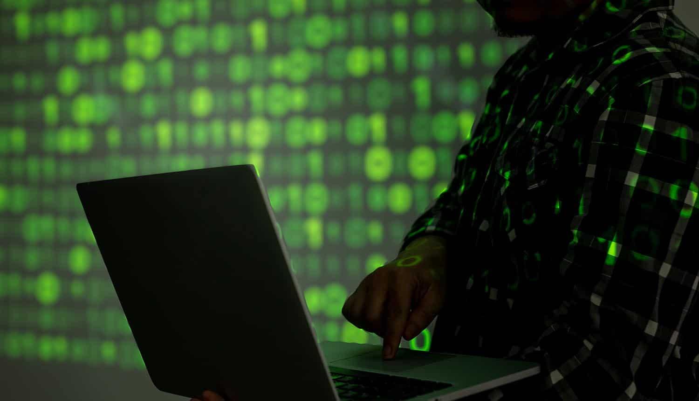 Dark web hacker using laptop showing Maze ransomware group shutting cyber crime operation