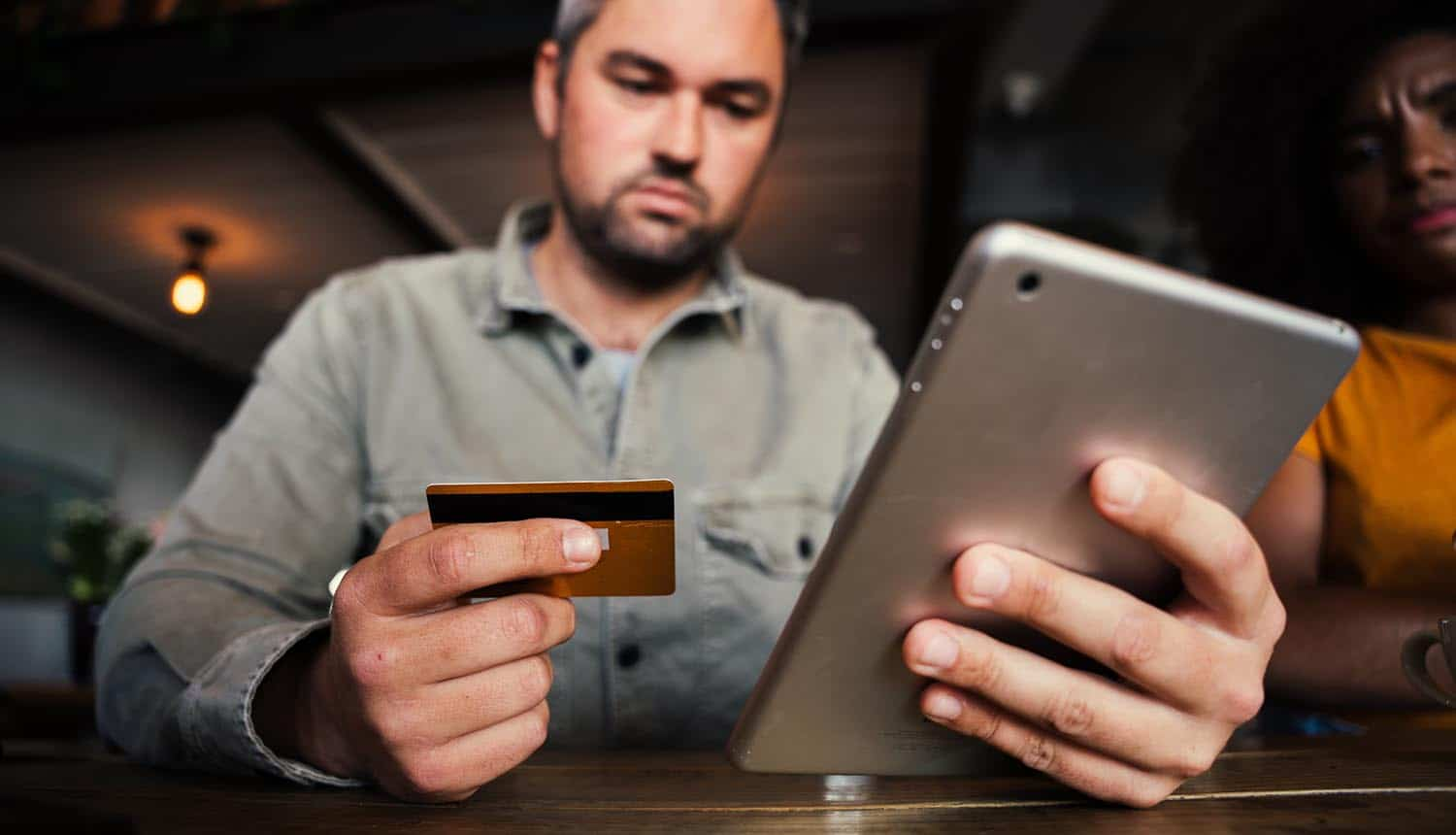 Man in coffee shop about to make an online payment with credit card