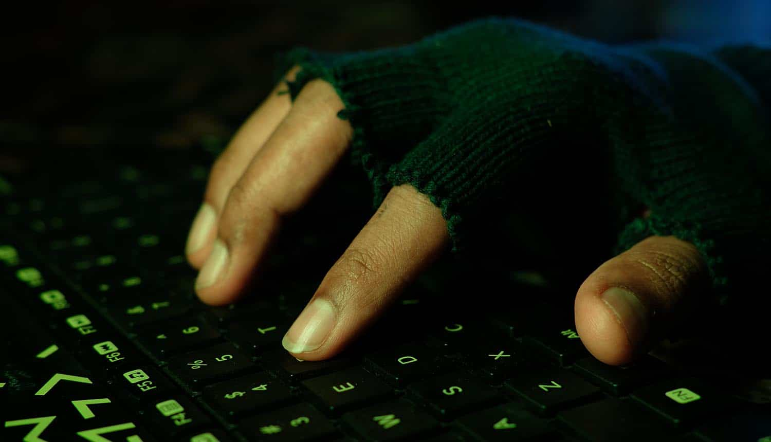 Hacker hand stealing data from laptop showing sale of data breach records on hacker forum