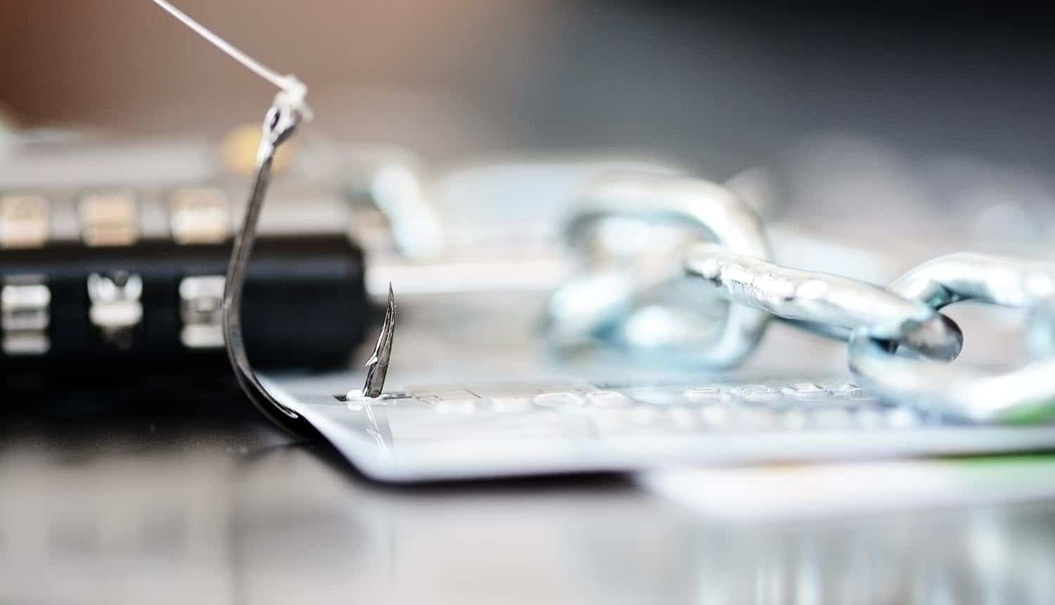 Padlock and chain near credit cards in fishing hook showing phishing attack