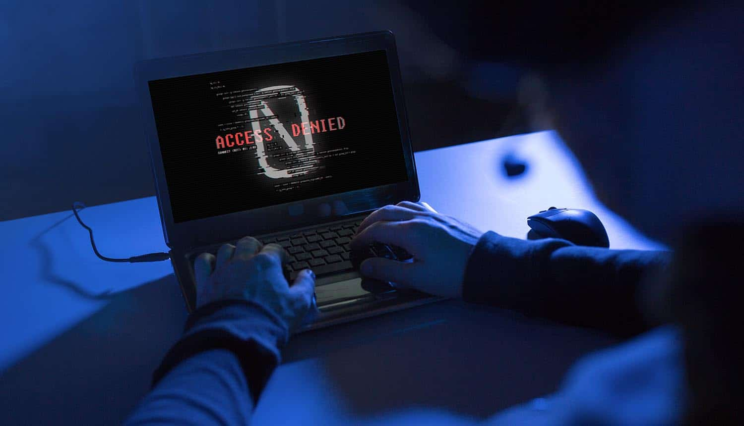 Hands of hacker with access denied message on laptop