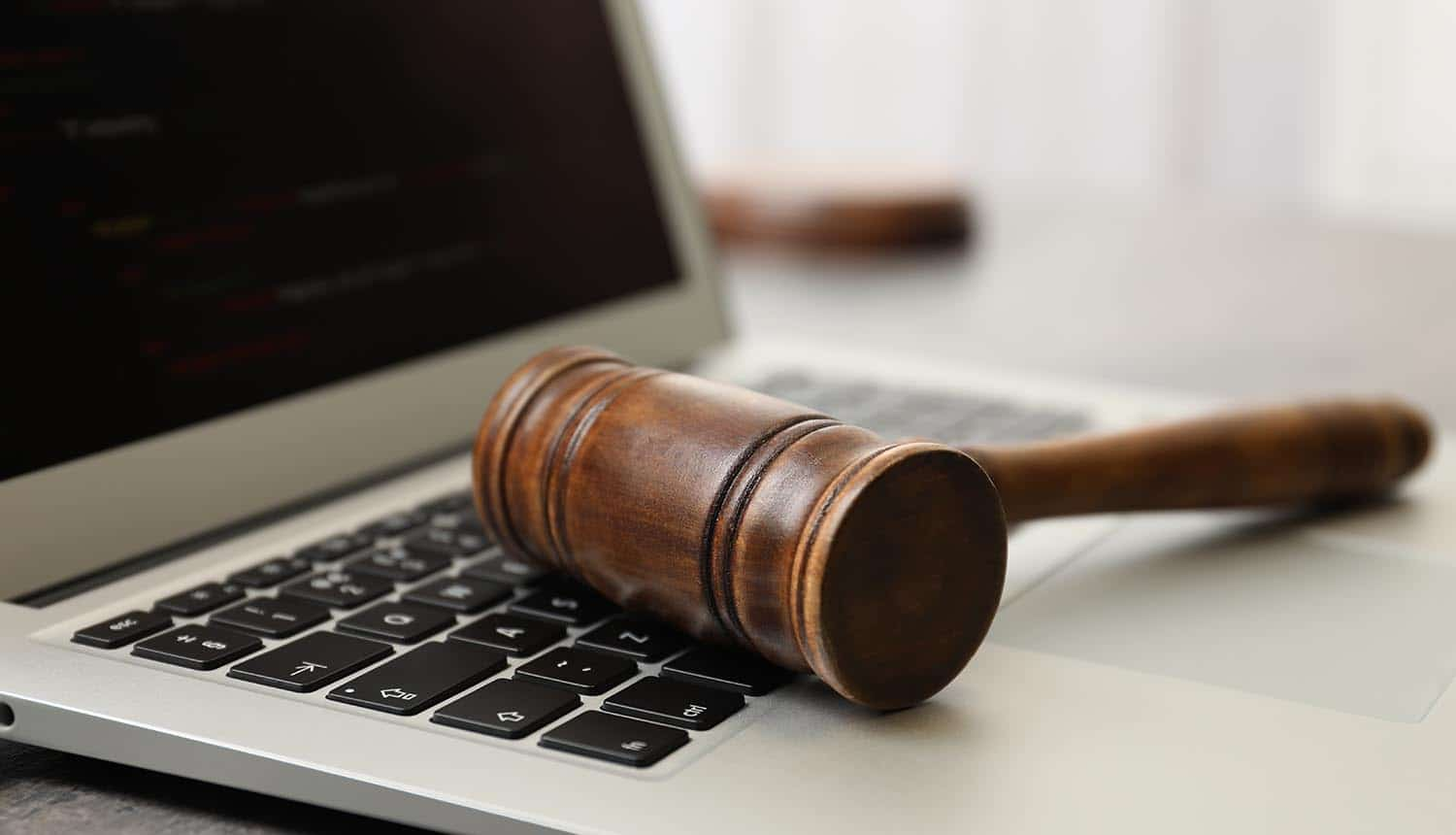 Laptop and gavel on table showing privacy complaints on adtech real time bidding